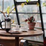 photo d'un café et 2 tasses sur une table dans une jolie verrière